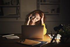 Femme de sourire parlant au téléphone tout en travaillant sur l'ordinateur portable Image stock