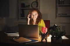 Femme de sourire parlant au téléphone tout en travaillant sur l'ordinateur portable Photographie stock