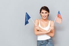 Femme de sourire patriote tenant l'Européen et les drapeaux des Etats-Unis Image stock