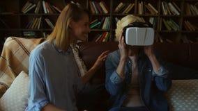 Femme de sourire pluse âgé examinant des verres de VR avec sa fille clips vidéos