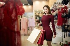 Femme de sourire portant quelques paniers avec l'étalage de magasin de lingerie sur le fond Fille caucasienne assez de sourire Photographie stock