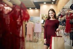 Femme de sourire portant quelques paniers avec l'étalage de magasin de lingerie sur le fond Fille caucasienne assez de sourire Photo stock