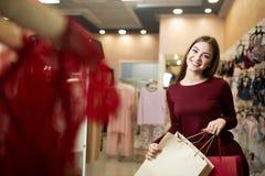 Femme de sourire portant quelques paniers avec l'étalage de magasin de lingerie sur le fond Fille caucasienne assez de sourire images stock