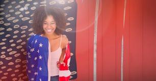Femme de sourire portant un drapeau américain sur ses épaules Images libres de droits