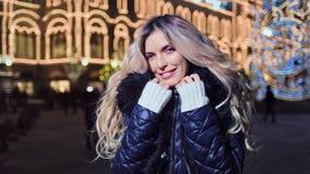 Femme de sourire de portrait belle posant regardant la caméra à l'arrière-plan de lumières de maison d'illumination clips vidéos