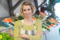 Femme de sourire de portrait dans le tablier vendant des veggies Photo libre de droits