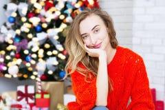 Femme de sourire de portrait sur le fond intérieur de Noël Concept d'an neuf Foyer sélectif Arbre et guirlandes de Noël image stock