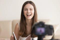 Femme de sourire positive parlant sur l'appareil-photo, critique de livre de enregistrement photos stock
