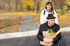 Femme de sourire poussant un vieil homme dans un fauteuil roulant Photo stock