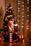 Femme de sourire près de présent d'ouverture d'arbre de Noël Photographie stock libre de droits