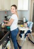 Femme de sourire préparant la nourriture pour ses 9 mois de bébé garçon Photographie stock libre de droits