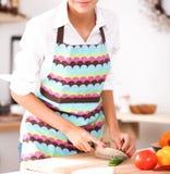Femme de sourire préparant la salade dans la cuisine Images libres de droits