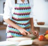 Femme de sourire préparant la salade dans la cuisine image stock