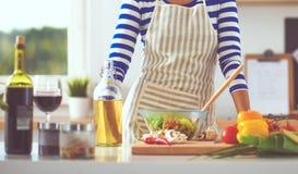 Femme de sourire préparant la salade dans la cuisine image libre de droits