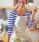 Femme de sourire préparant la salade dans la cuisine photographie stock libre de droits