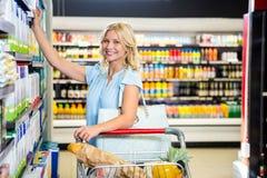 Femme de sourire prenant la nourriture de l'étagère Image stock