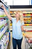 Femme de sourire prenant la nourriture de l'étagère Photographie stock libre de droits