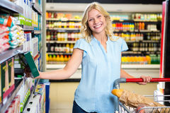 Femme de sourire prenant la nourriture de l'étagère Photo libre de droits