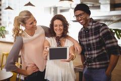Femme de sourire prenant le selfie avec des amis de comprimé numérique au café Images stock