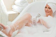 Femme de sourire prenant un bain photographie stock libre de droits