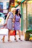 Femme de sourire regardant dans la fenêtre de boutique, extérieur coloré Image stock