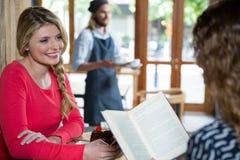 Femme de sourire regardant l'ami féminin dans le café Image stock