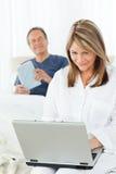 Femme de sourire regardant son ordinateur portatif Photos libres de droits