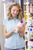 Femme de sourire regardant une bouteille à lait Images libres de droits
