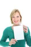 Femme de sourire retenant une page blanc Photo stock
