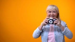 Femme de sourire de retraité prenant la photo avec la caméra, le passe-temps et la relaxation de cru images libres de droits