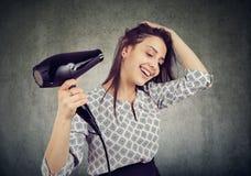 Femme de sourire séchant ses cheveux avec un hairdryer image stock