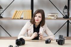 Femme de sourire s'asseyant à la table avec des appareils-photo photos libres de droits