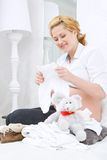 Femme de sourire s'asseyant avec des vêtements de bébé Photo stock