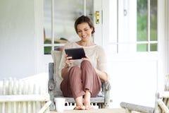 Femme de sourire s'asseyant avec le comprimé numérique Image libre de droits