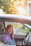 Femme de sourire s'asseyant dans la voiture prête à partir sur le voyage par la route photo libre de droits