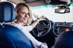 Femme de sourire s'asseyant dans le véhicule photographie stock libre de droits