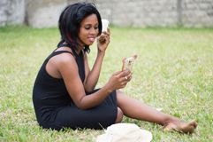 Femme de sourire s'asseyant dans un jardin utilisant un téléphone portable pour le communi image stock