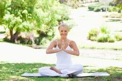 Femme de sourire s'asseyant en position de yoga sur la pelouse Photos stock