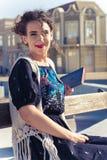 Femme de sourire s'asseyant et posant sur le banc dans la vieux ville et Re photo stock