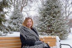femme de sourire s'asseyant sur le banc de parc Chicago avec la chute de neige Photo stock