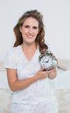 Femme de sourire s'asseyant sur le lit tenant le réveil Images stock
