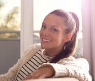 Femme de sourire s'asseyant sur le sofa photos libres de droits