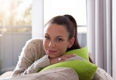 Femme de sourire s'asseyant sur le sofa photos stock