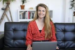Femme de sourire s'asseyant sur un sofa à la maison utilisant un ordinateur portable photographie stock