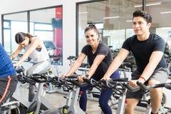 Femme de sourire s'exerçant sur le vélo de rotation avec des amis image libre de droits