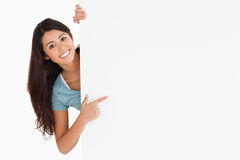 Femme de sourire se dirigeant à un panneau Photographie stock libre de droits