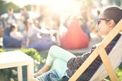 Femme de sourire se reposant sur la chaise de plate-forme Photographie stock libre de droits