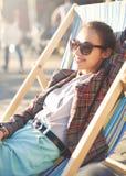 Femme de sourire se reposant sur la chaise de plate-forme Photos libres de droits