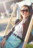 Femme de sourire se reposant sur la chaise de plate-forme Photographie stock
