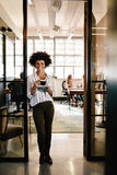 Femme de sourire se tenant en porte de bureau avec du café Photo stock